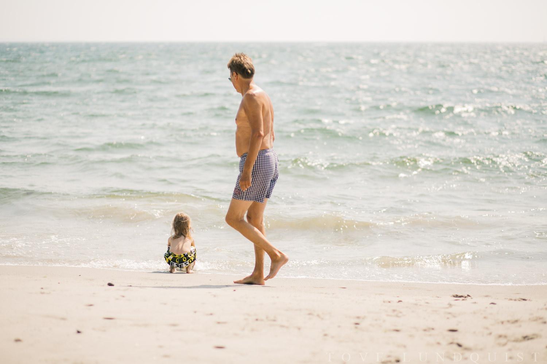 Dokumentärt fotografi i färg från stranden under en familjefotografering. Tove Lundquist är en dokumentär familjefotograf som är verksam i Skåne. Stort fokus på storytelling och naturliga känslor. Dokumenterar vardagen. Ej poserat.